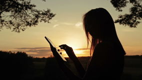 Female silhouette using a digital tablet in the forest at sunset stock video