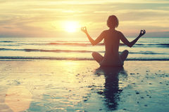 Female silhouette in yoga meditation pose. At amazing sunset on the sea stock photography