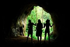 Female silhouettes at the entrance to natural cave in the forrest royalty free stock photography