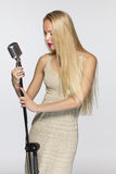 Female with silver microphone. Elegant blond female with silver microphone stock photo
