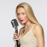 Female with silver microphone. Elegant blond female with silver microphone looking at camera stock photos
