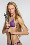 Female with silver microphone. Sensual blond female in lilac bikin with silver microphone royalty free stock photos