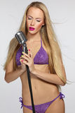 Female with silver microphone. Sensual blond female in lilac bikin with silver microphone royalty free stock photography