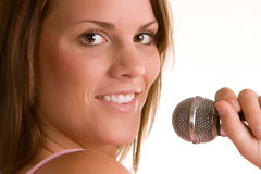 Female Singer. Young woman with microphone on white background Stock Image
