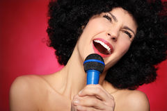 Female singer. Young woman over red background Royalty Free Stock Photo