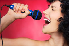 Female singer. Young woman over red background Royalty Free Stock Photography