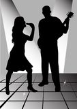 Female singer. And man playing guitar Stock Photo