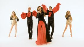 A female singer in a black and red suit singing in the studio on a white background. With her stands a group of. A group of professional actors dancing on a stock video footage
