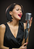 Female singer with closed eyes keeping microphone stock photo