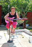 Female singer and guitarist. Photo of woman seated having fun singing and playing a pink inflatable guitar Stock Images