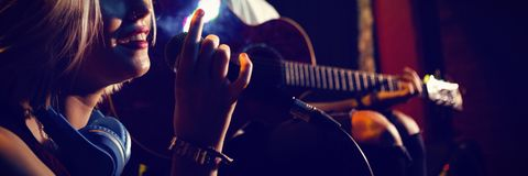 Female singer with guitarist on stage. Female singer with guitarist performing on stage at nightclub Stock Photos