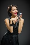 Female singer handing mic Stock Photo