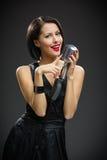 Female singer handing mic Stock Photo