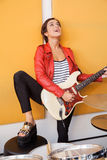 Female Singer With Leg On Table Playing Guitar Stock Photography