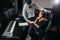 Female singer listen song record in music studio. Female singer in headphones listen to song record against sound producer in music studio. Professional digital royalty free stock images