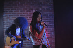 Female singer with male guitarist performing at music concert Stock Image