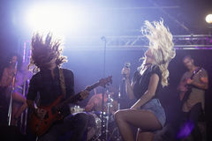 Female singer and male guitarist with tousled hair performing at nightclub. Female singer and male guitarist with tousled hair performing together on stage at Stock Images