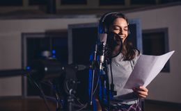 Female singer with microphone and reading lyrics. Smiling female singer with microphone and reading lyrics. Woman recording a song in music studio. Female royalty free stock photos