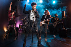 Female singer with microphone and rock and roll band performing hard rock music. On stage Stock Photography