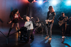 Female singer with microphone and rock and roll band playing hard rock music royalty free stock images