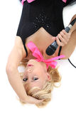 Female singer mith mic lying Royalty Free Stock Images