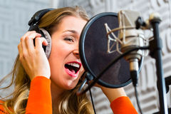 Female Singer or musician for recording in Studio. Young female singer or musician with microphone and headphone for audio recording in the Studio Stock Image