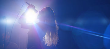 Female singer at nightclub. Cheerful female singer at nightclub during music festival Royalty Free Stock Image