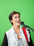 Female Singer Performing Against Green Wall royalty free stock photography