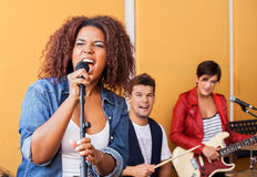 Female Singer Performing With Band Members In. Passionate female singer performing with band members in recording studio Royalty Free Stock Photo