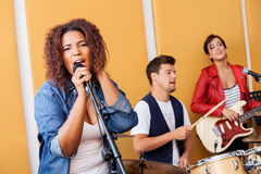 Female Singer Performing With Band In Recording. Passionate female singer performing with band in recording studio Stock Images