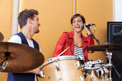 Female Singer Performing While Looking At Male Drummer. Happy female singer performing while looking at male drummer in studio Royalty Free Stock Photography