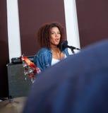 Female Singer Performing In Recording Studio Stock Photo