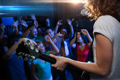 Female singer playing guitar over happy fans crowd. Holidays, music, nightlife and people concept - close up of singer playing electric guitar and singing on Stock Photos