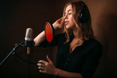Female singer recording a song in music studio. Woman vocalist in headphones against microphone. Audio recording. Professional digital sound technologies royalty free stock photography