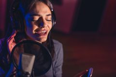 Female singer recording a song in studio Royalty Free Stock Photo