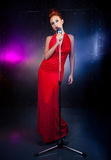 Female singer red dress; vintage microphone Stock Images