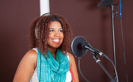 Female Singer Smiling While Performing In Studio Royalty Free Stock Photography