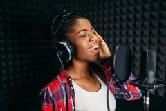 Female singer songs in audio recording studio. Female singer in headphones songs in audio recording studio. Musician listens composition, professional music stock images