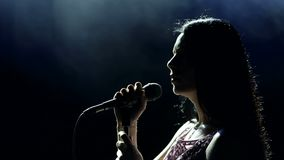 Female singer on the stage holding a microphone. Portrait of a beautiful singer with long hair on a dark smoky stage in the spotlight. Female singer on the stock footage