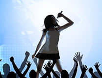 Female singer on stage. Performing in front of a crowd Stock Photos