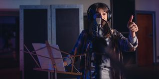 Female singer with thumbs up sign in recording studio Stock Images