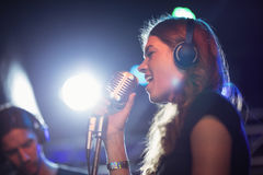 Female singer wearing headphones while singing at nightclub. Low angle view of female singer wearing headphones while singing at nightclub Royalty Free Stock Photo