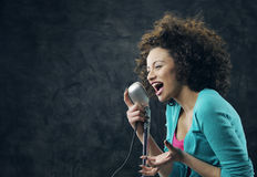 Female singer. Young female singer with brown curly hair singing a song Royalty Free Stock Photo