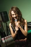 Female singing into mic. Royalty Free Stock Image