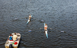 Female single scull rowing competitors in training. Stock Photography