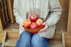 Female sits on porch and holds bowl with apples close up Stock Images