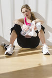 Female sitting against wall in after workout Stock Photography