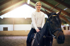 Female sitting astride in indoor riding hall. Blonde female sitting astride dark horse in indoor riding hall Royalty Free Stock Photo