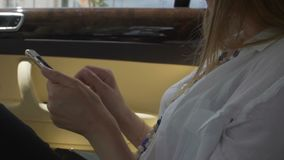 Female sitting at back seat of expensive car, taking cellphone, rush hour. Stock footage stock footage