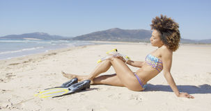 Female sitting on beach with flippers Stock Image